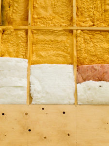 Different types of building insulation: polyurethane spray foam and fiberglas mats.